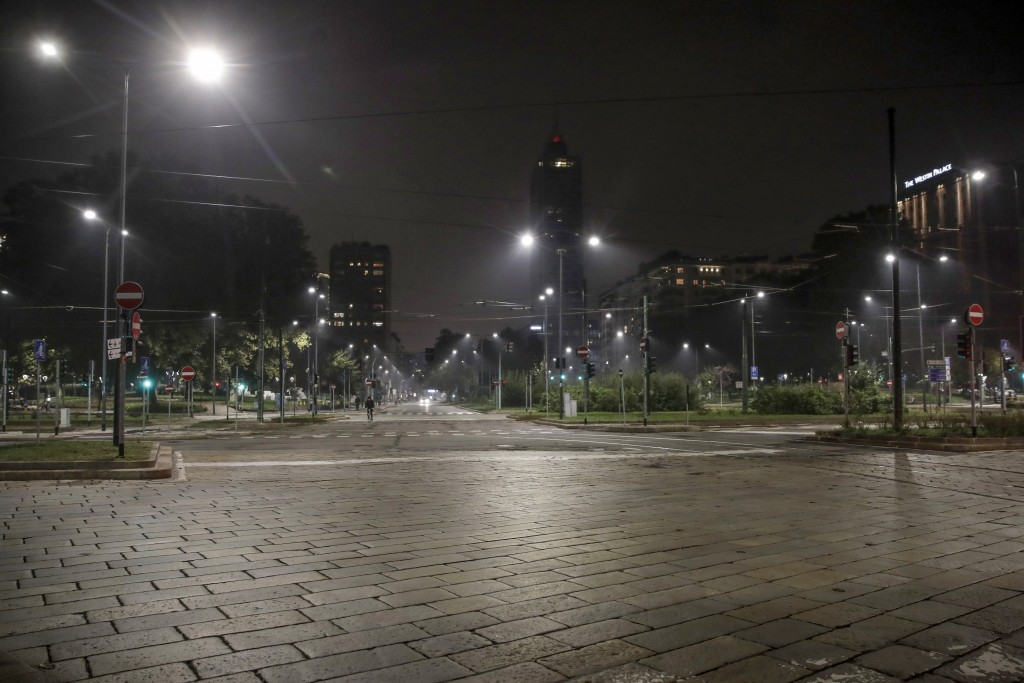 An empty street is lit by street lights in Milan, northern Italy, Sunday, Oct. 25, 2020. Since the 11 p.m.-5 a.m. curfew took effect last Thursday, pe...