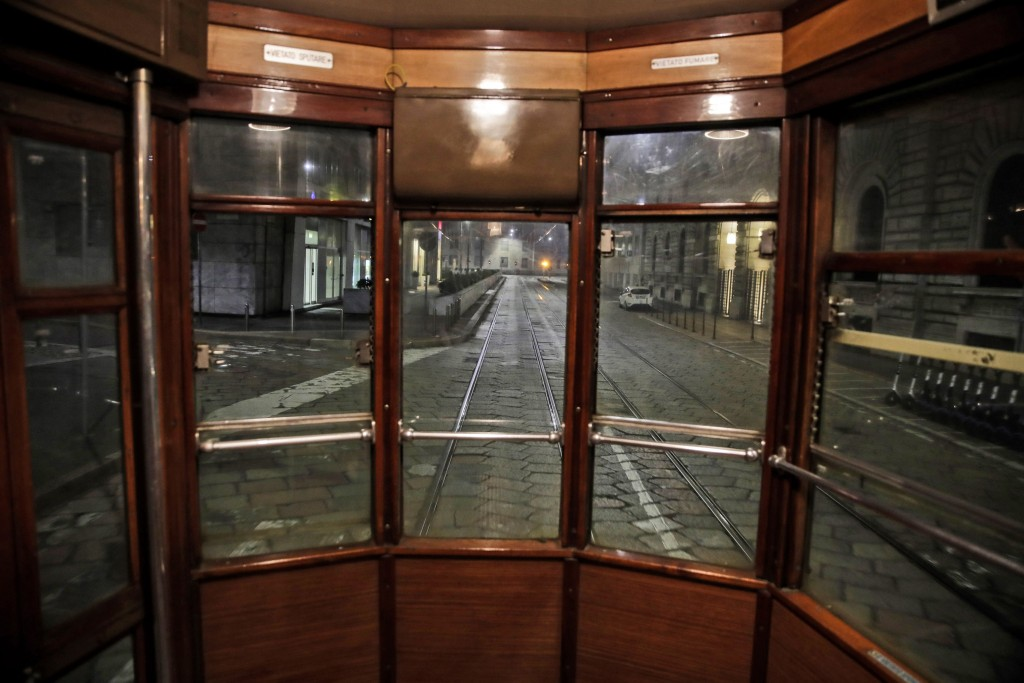 An empty street is seen from a tram streetcar window, in Milan, northern Italy, early Sunday, Oct. 25, 2020. Since the 11 p.m.-5 a.m. curfew took effe...