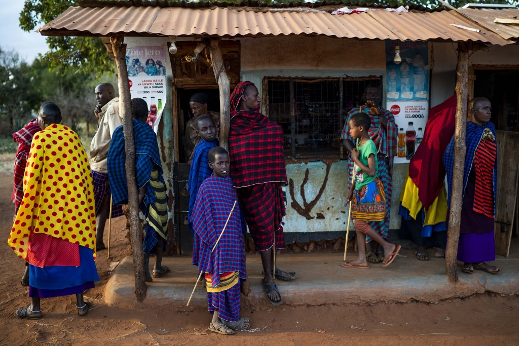 FILE - In this Friday, July 5, 2019 file photo, Maasai tribesmen hang out in the village of Loibor Siret, Tanzania. Tanzanians are due to go to the po...