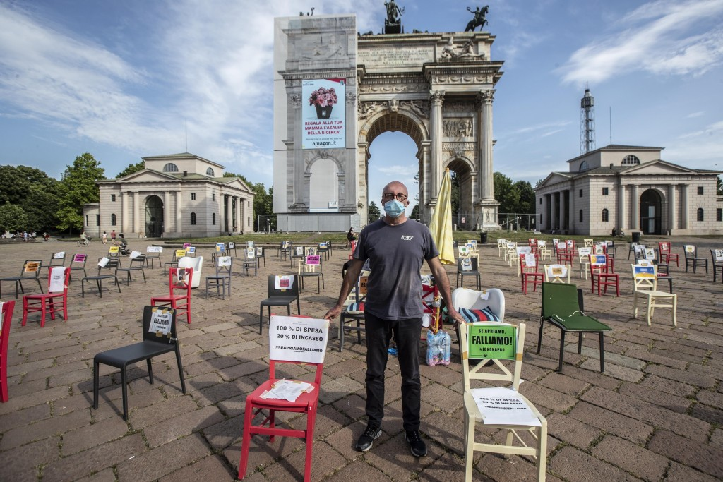 FILE - In this Saturday, May 9, 2020 file photo, restaurant owner Paolo Polli stages a protest in Milan, Italy. The coronavirus pandemic is gathering ...