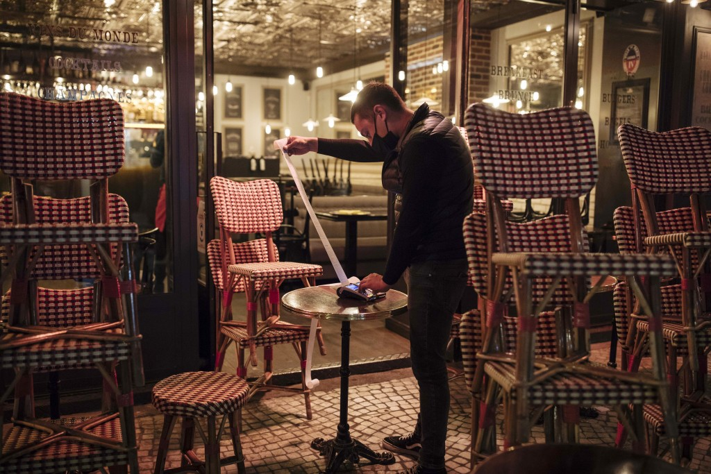 FILE - In this Oct. 17, 2020 file photo, a waiter checks the final revenue as he closes a bar terrace in Paris. The coronavirus pandemic is gathering ...