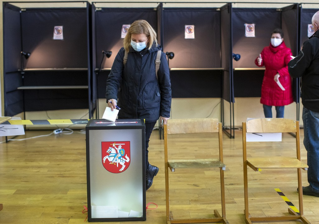 A woman, wearing face masks to protect against coronavirus, casts her ballot at a polling station during the second round of a parliamentary election ...