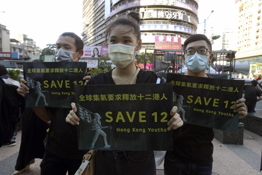 Supporters gather, holding slogan to demand the release of the 12 Hong Kong protesters that have been arrested by mainland Chinese authorities, in Tai...