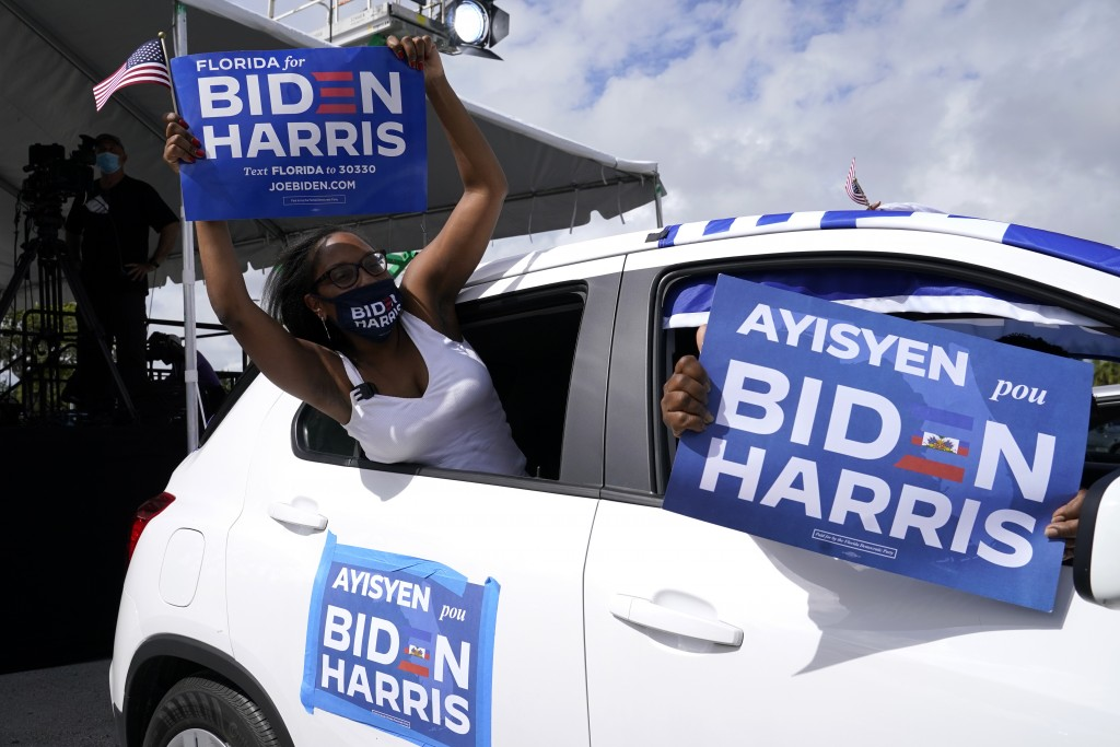 Nashley Harrigan, who is of Haitian descent, cheers from her vehicle at a car rally before a speech by former President Barack Obama who is campaignin...