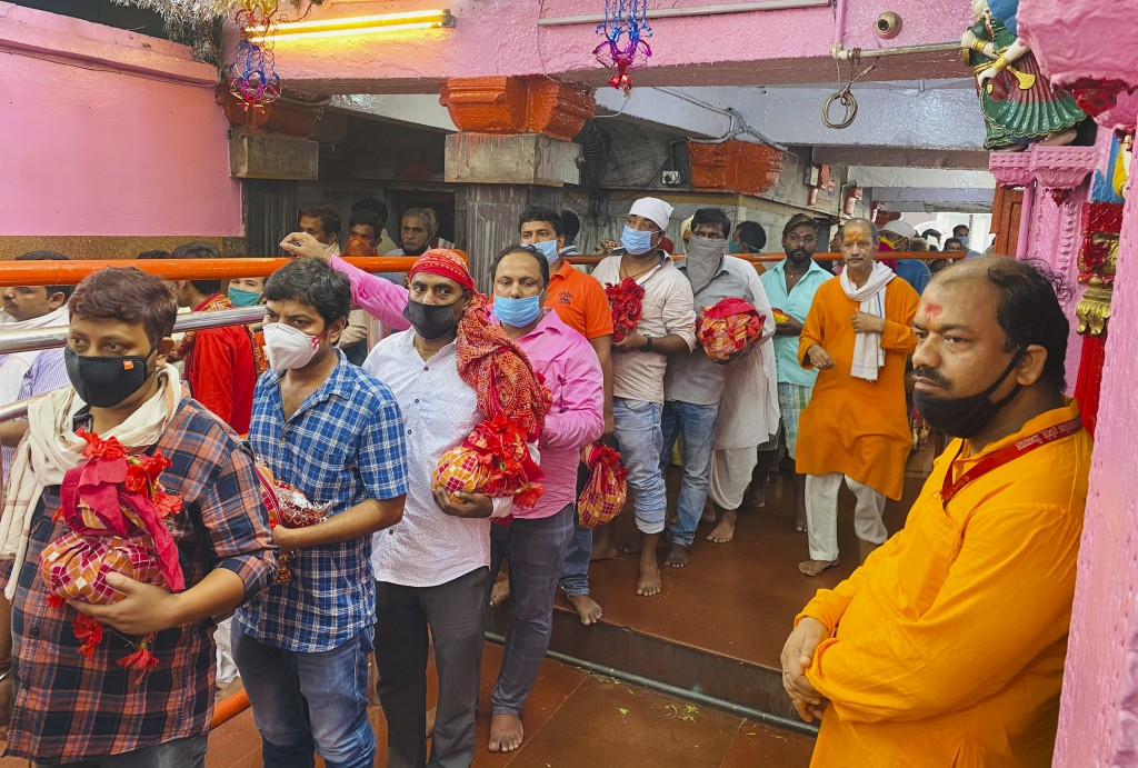 FILE- In this Saturday, Oct. 17, 2020, file photo, devout Hindus wearing masks as a precaution against the coronavirus stand in a queue to offer praye...