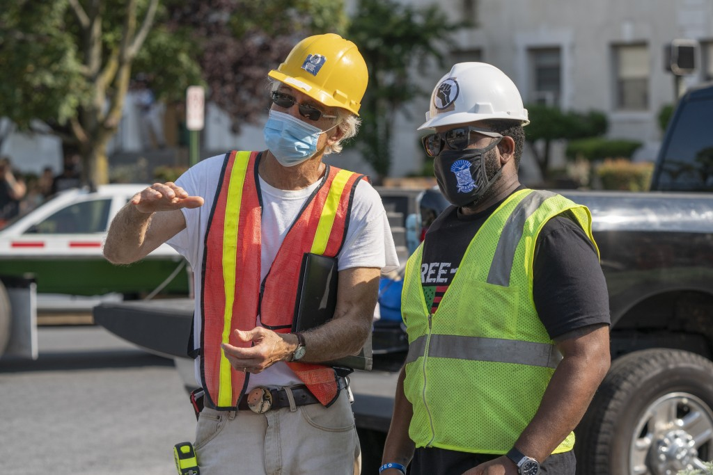In this photo provided by Sanjay Suchak, Richmond sculptor Paul DiPasquale, left, talks with Devon Henry during the removal of the J.E.B. Stuart statu...