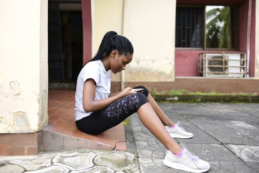 In this photo taken on Wednesday, Oct. 14, 2020, Dodeye Ewa, 16 year old, read a message on her mobile phone outside her house in Calabar, Nigeria. Th...