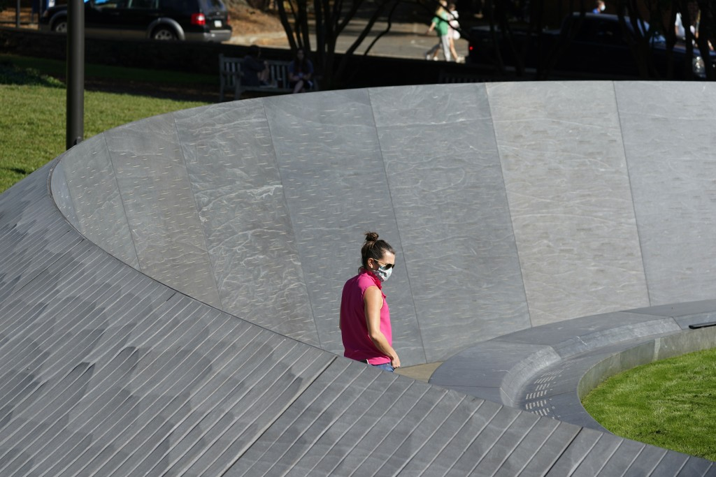 A visitor looks over inscriptions on the walls of the Memorial to Enslaved Laborers at the University of Virginia in Chrlottesville, Va., Friday Oct. ...