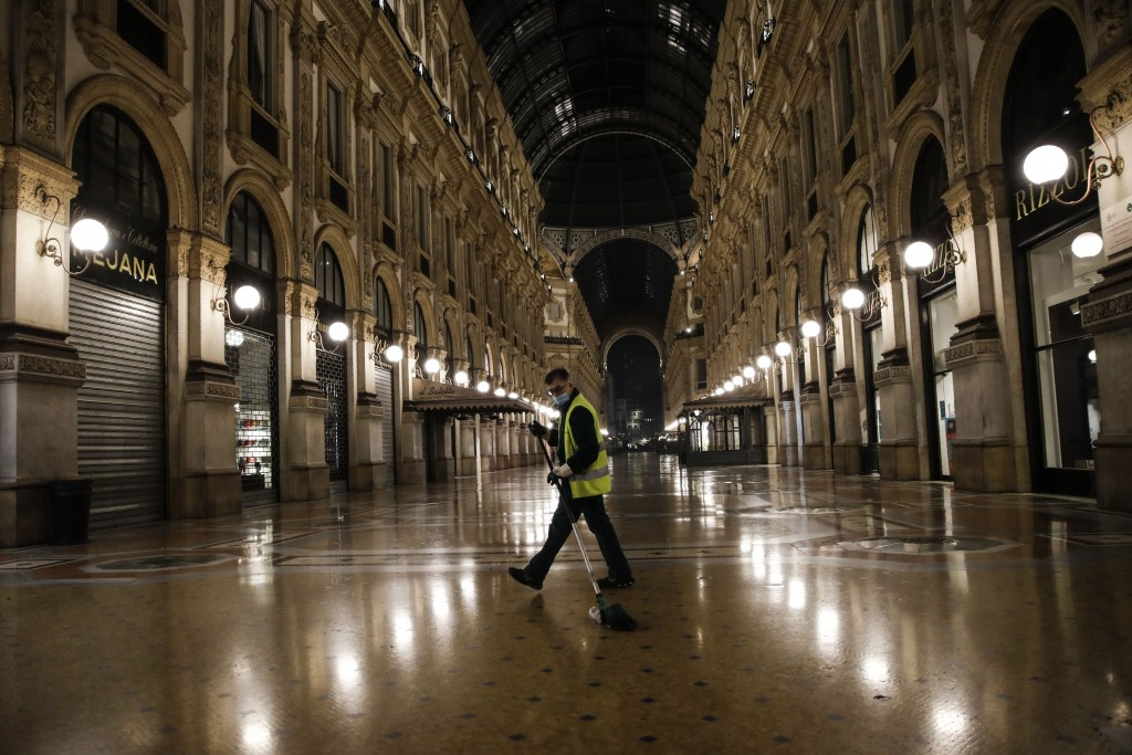 A cleaner sweeps in an empty Vittorio Emanuele II arcarde, in Milan, northern Italy, early Sunday, Oct. 25, 2020. Since the 11 p.m.-5 a.m. curfew took...