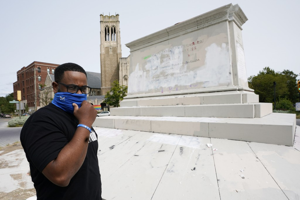 Devon Henry, owner of Henry Enterprises, adjusts his mask in front of the pedestal that used to hold the statue of Confederate General J.E.B Stuart du...