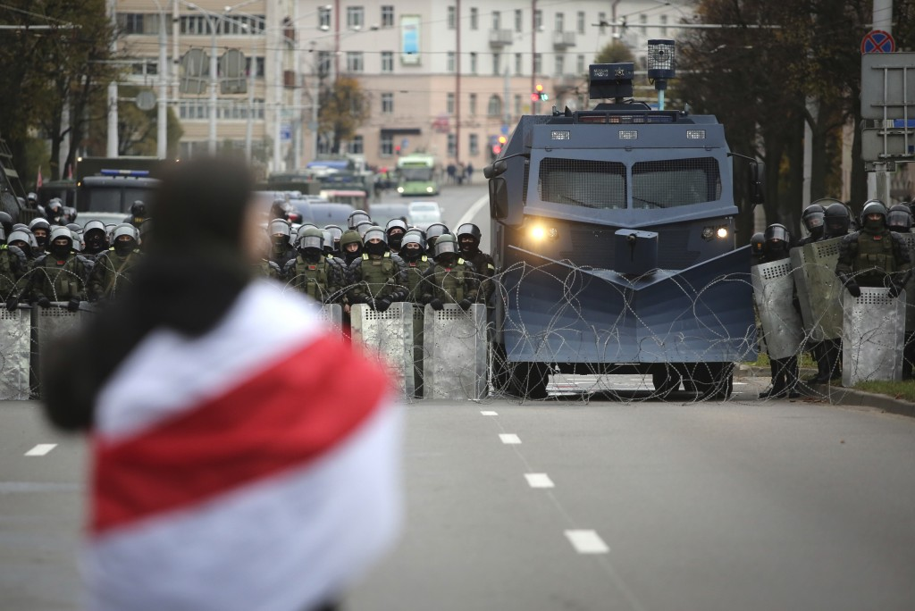 A protester draped in an old Belarusian national flag stands in front of a police line during an opposition rally to protest the official presidential...