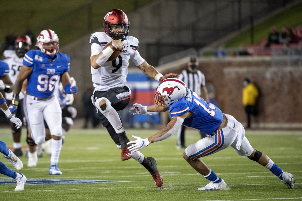 Cincinnati quarterback Desmond Ridder (9) evades the tackle of SMU safety Roderick Roberson, Jr. (13) on a touchdown run during the second half of an ...