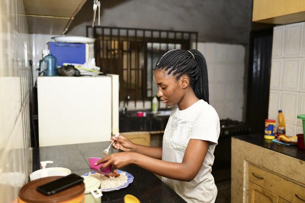 In this photo taken on Wednesday, Oct. 14, 2020, Dodeye Ewa, 16 year old serve breakfast at inside the kitchen in Calabar, Nigeria. The third child is...