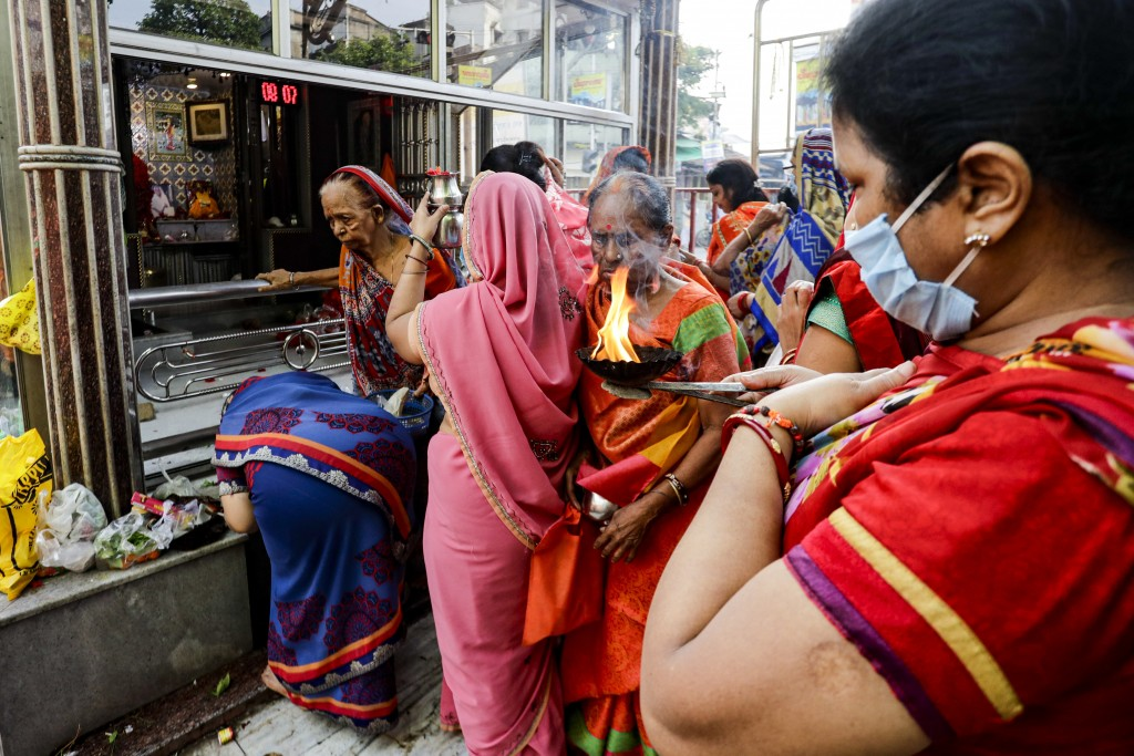 FILE- In this Saturday, Oct. 17, 2020, file photo, Hindu women, some wearing face masks to prevent the spread of the coronavirus, perform rituals outs...