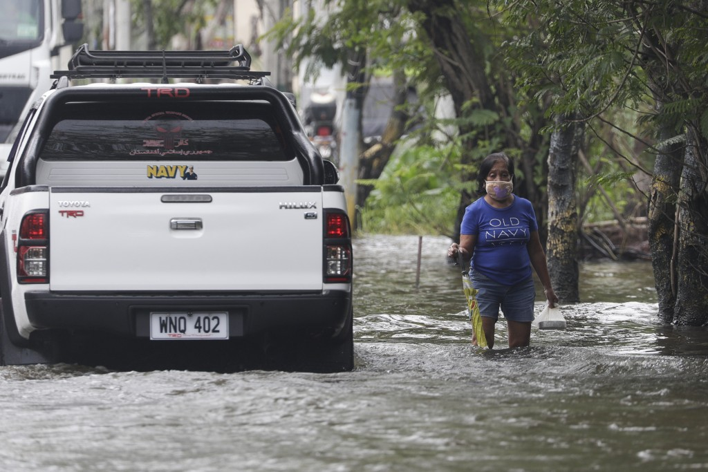 A resident negotiates a flooded road due to Typhoon Molave in Pampanga province, northern Philippines on Monday, Oct. 26, 2020. A fast moving typhoon ...