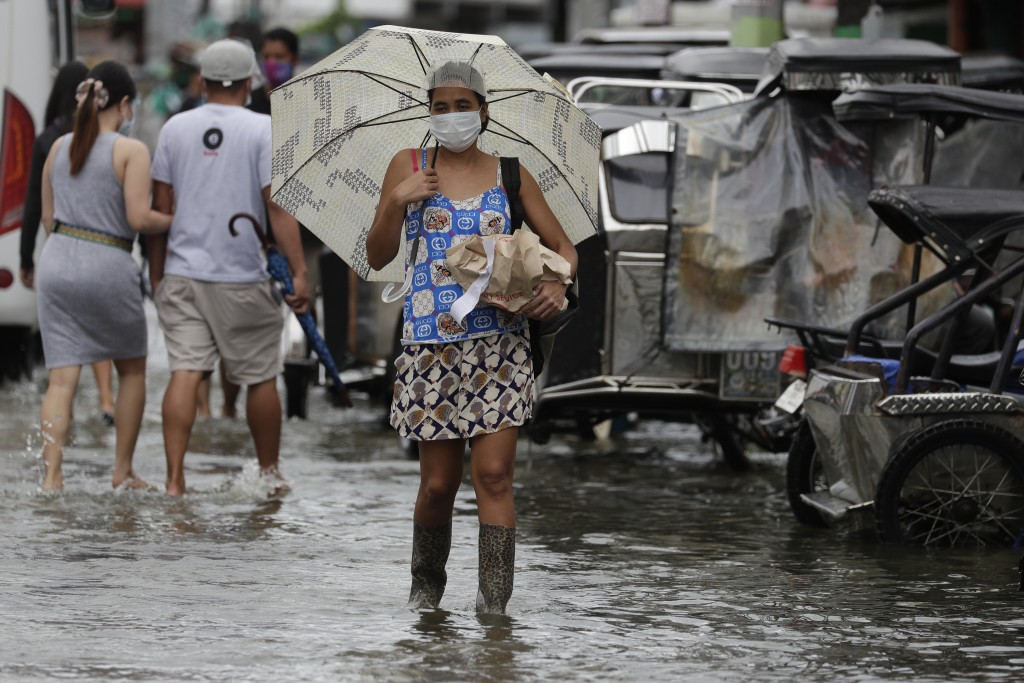 A woman wearing masks to prevent the spread of the coronavirus carries items as she wades along a flooded road due to Typhoon Molave in Pampanga provi...