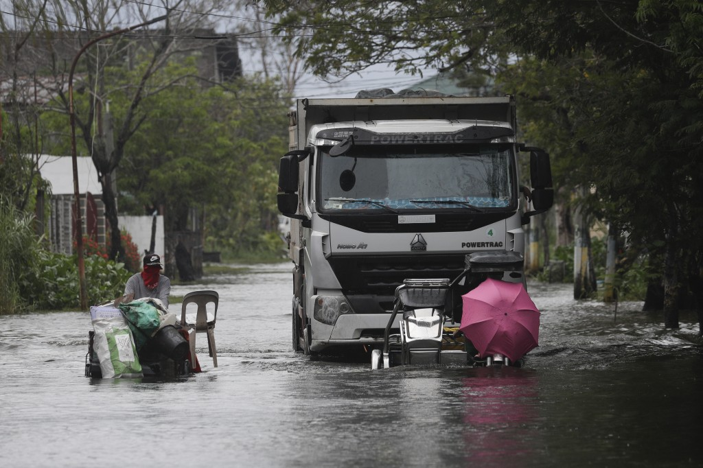 Motorists with an umbrella negotiate a flooded road due to Tyophoon Molave in Pampanga province, northern Philippines, Monday, Oct. 26, 2020. A fast-m...