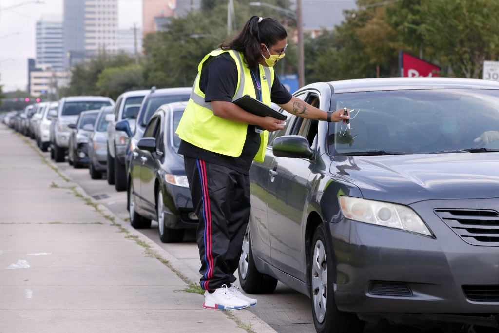 Volunteer Sharely Gomez marks the windshield after taking information from clients in their cars as they wait in line in before the food distribution ...