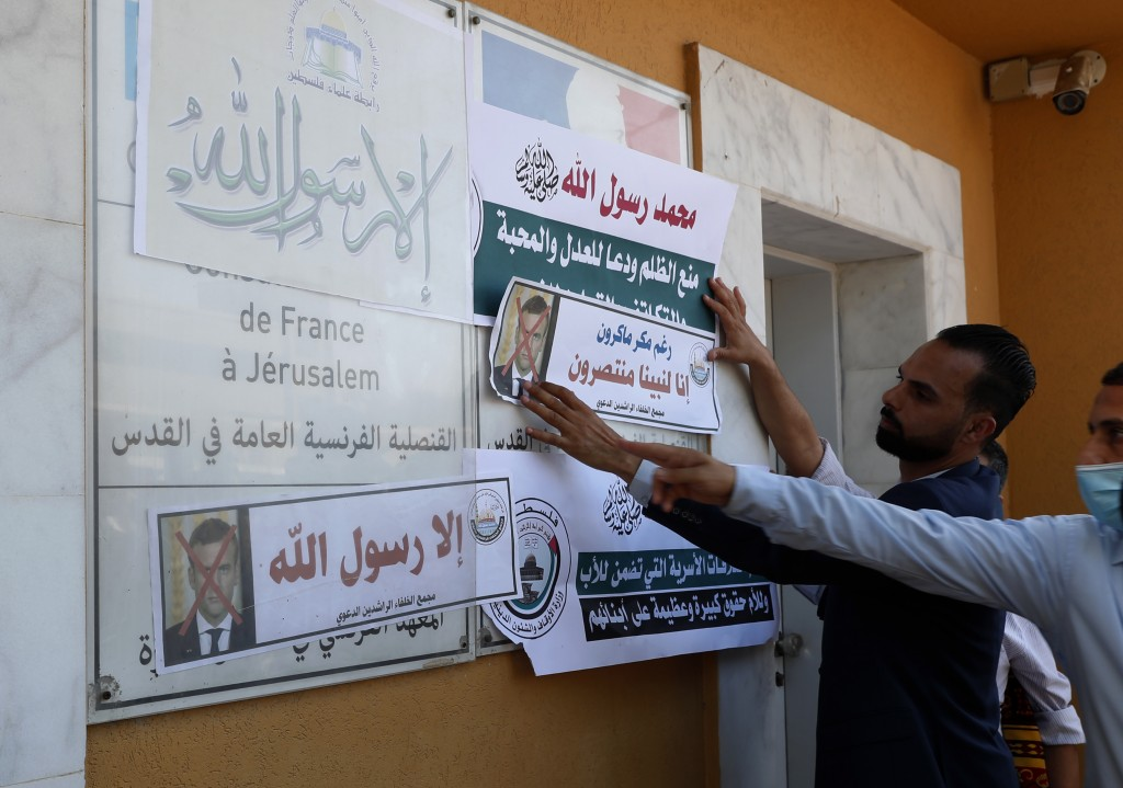 An Islamic scholar posts defaced pictures of French President Emmanuel Macron at the entrance of the French Cultural center during a protest against t...