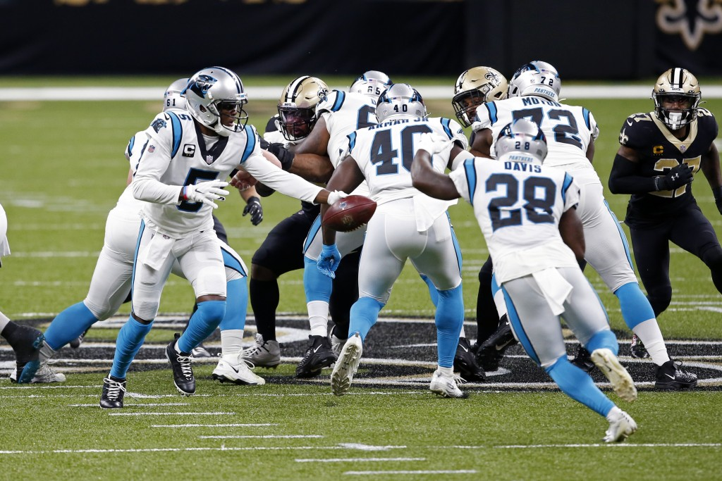 Carolina Panthers quarterback Teddy Bridgewater (5) hands off to running back Mike Davis (28) in the first half of an NFL football game against the Ca...