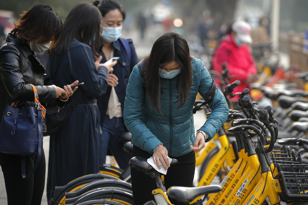 A woman wearing a face mask to help curb the spread of the coronavirus uses an alcohol tissue to disinfect a bicycle of bike-sharing companies during ...