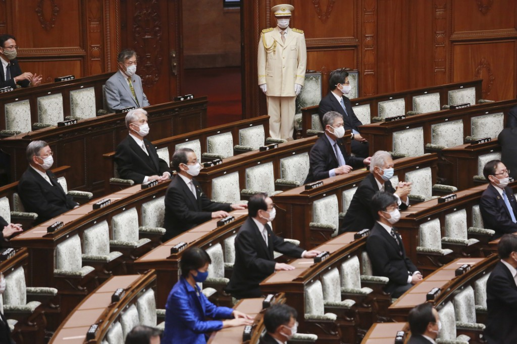 Japanese lawmakers wearing face masks to protect against the spread of the coronavirus attend an extraordinary Diet session at the upper house of parl...