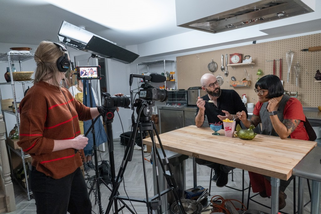 In this Oct. 7, 2020 photo, producer Jessica Opon, left, films Andrew Rea, founder of the Binging with Babish network, center, as he tastes popcorn ic...