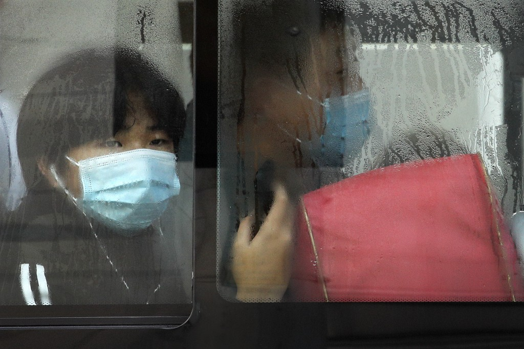 A commuter wearing a face mask to help curb the spread of the coronavirus looks out from a traveling bus during the morning rush hour in Beijing, Mond...