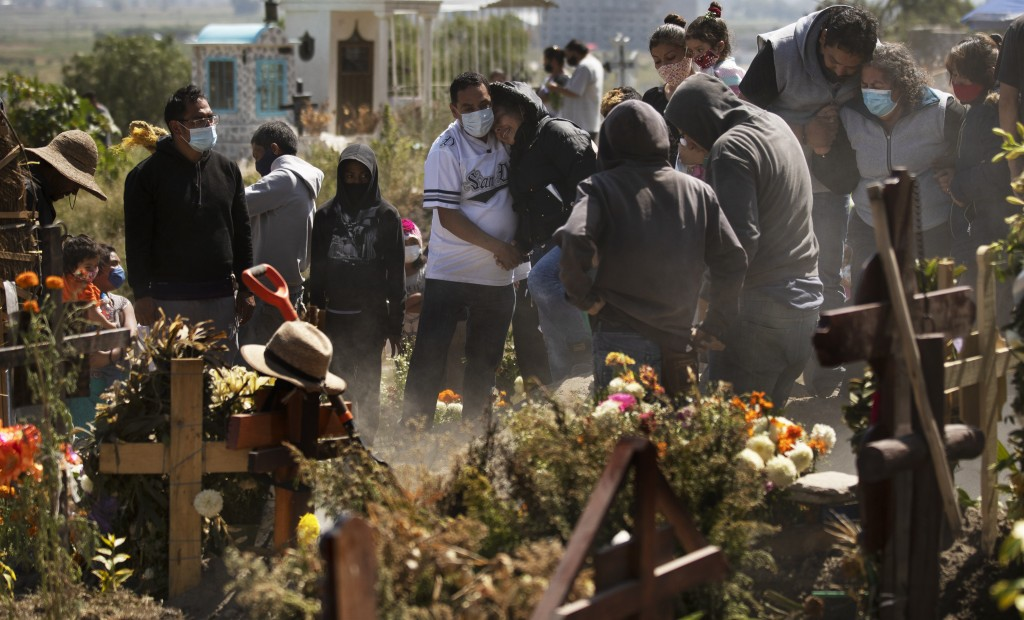Relatives bury Isaac Nolasc,o who died of reasons not believed related to COVID-19, in a section of the municipal cemetery of Valle de Chalco amid the...