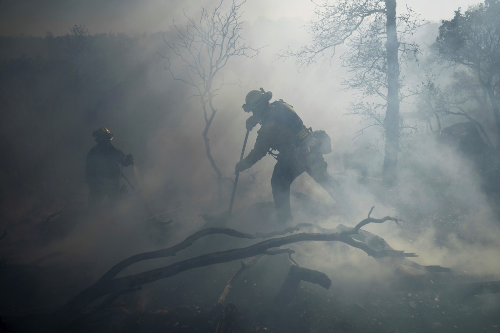 A firefighter extinguishes hotspots while battling the Olinda Fire in Anderson, Calif., Sunday, Oct. 25, 2020. The blaze was one of four fires burning...