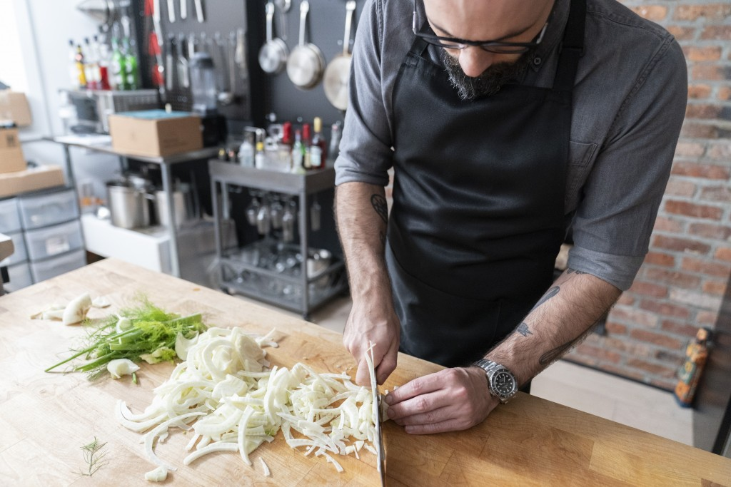"In this Oct. 7, 2020 photo, Andrew Rea, founder of the Binging with Babish network, chops a fennel as he tapes an episode of ""Binging with Babish,"" in..."