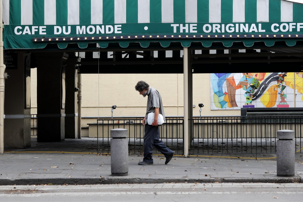 FILE - In this Friday, March 27, 2020, file photo, a man walks past the closed Cafe Du Monde restaurant in the French Quarter of New Orleans. Prospect...