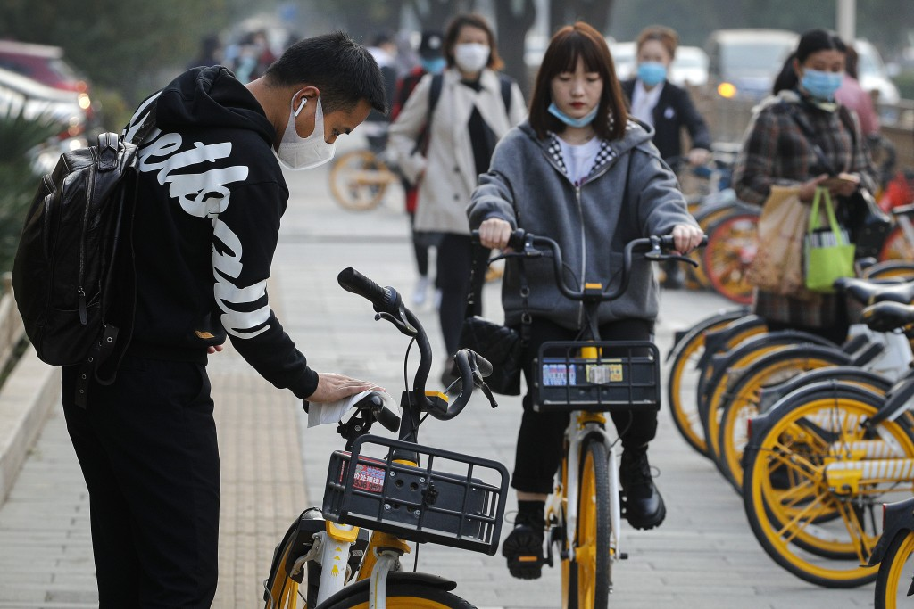 A man wearing a face mask to help curb the spread of the coronavirus uses an alcohol tissue to disinfect a bicycle of bike-sharing companies during th...