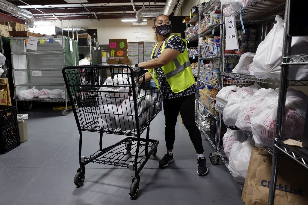 Evelyn Gomez places pre-filled bags of groceries from the indoor pantry into a shopping cart to easily take them outside to the drive thru distributio...