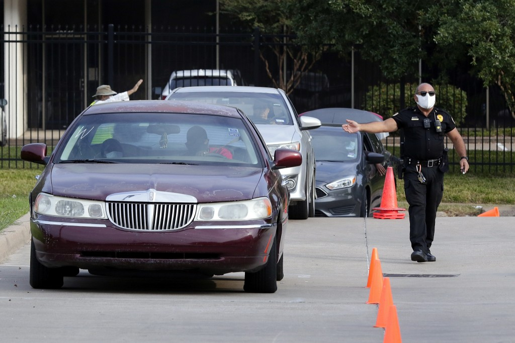 Security Officer Amer Alani directs traffic into the drive thru line as food distribution to clients gets underway at the West Houston Assistance Mini...