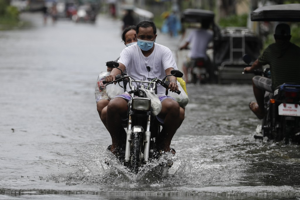 Residents on a motorcycle negotiate a flooded road due to Typhoon Molave in Pampanga province, northern Philippines, Monday, Oct. 26, 2020. A fast-mov...