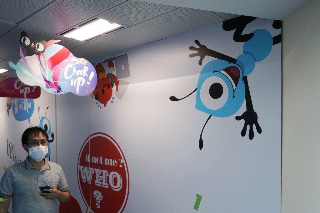 In this Friday, Oct. 23, 2020 photo, an employee walks past the picture of Ant Group's mascot at the Ant Group office in Hong Kong. China's Ant Group ...