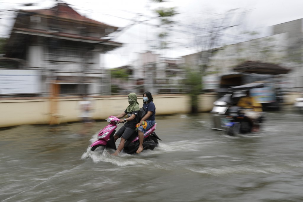 Residents wear masks to prevent the spread of the coronavirus ride motorcycles as they negotiate a flooded road due to Typhoon Molave in Pampanga prov...