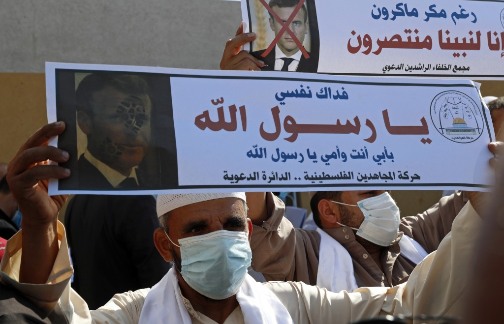 Islamic scholars hold defaced pictures of French President Emmanuel Macron during a protest against the publishing of caricatures of the Prophet Muham...