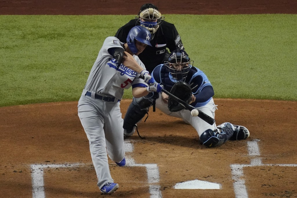 Los Angeles Dodgers' Corey Seager hits a RBI-single against the Tampa Bay Rays during the first inning in Game 5 of the baseball World Series Sunday, ...