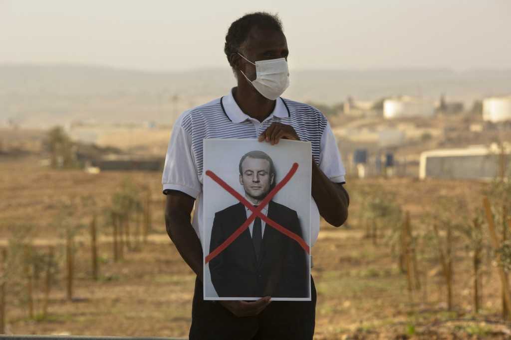 An Israeli Arab protester wears a face masks to help prevent the cooranvirus while holding a defaced picture of French President Emmanuel Macron, duri...