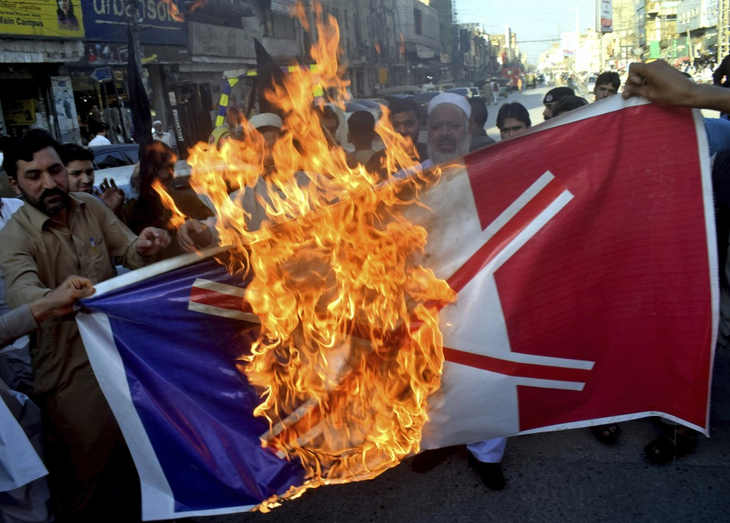 Pakistan traders burn burn a representation of the French flag during a protest against the publishing of caricatures of the Prophet Muhammad they dee...