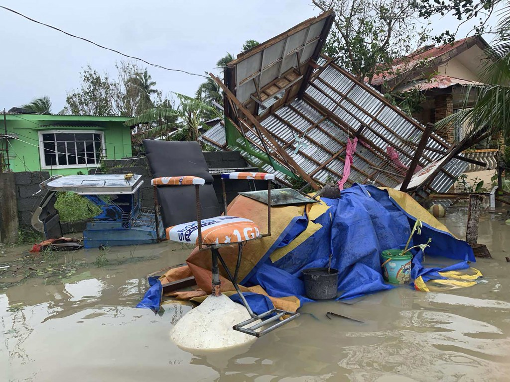 The remains of a barbershop is surrounded by floods in Pola town on the island of Mindoro, central Philippines, Monday, Oct. 26, 2020. A fast-moving t...