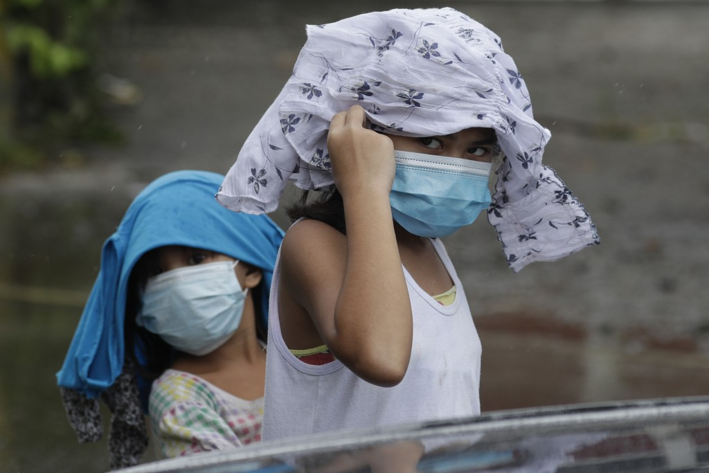 Young girls wearing masks to prevent the spread of the coronavirus place clothes to shelter them from rain due to Typhoon Molave in Pampanga province,...