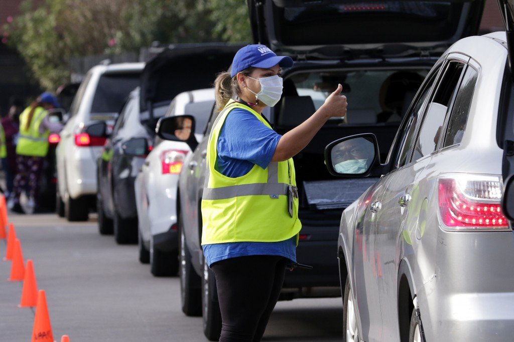 Lisa Iparrea, director of client services, gives a thumbs up as she helps direct cars through the touchless drive thru food distribution line at the W...