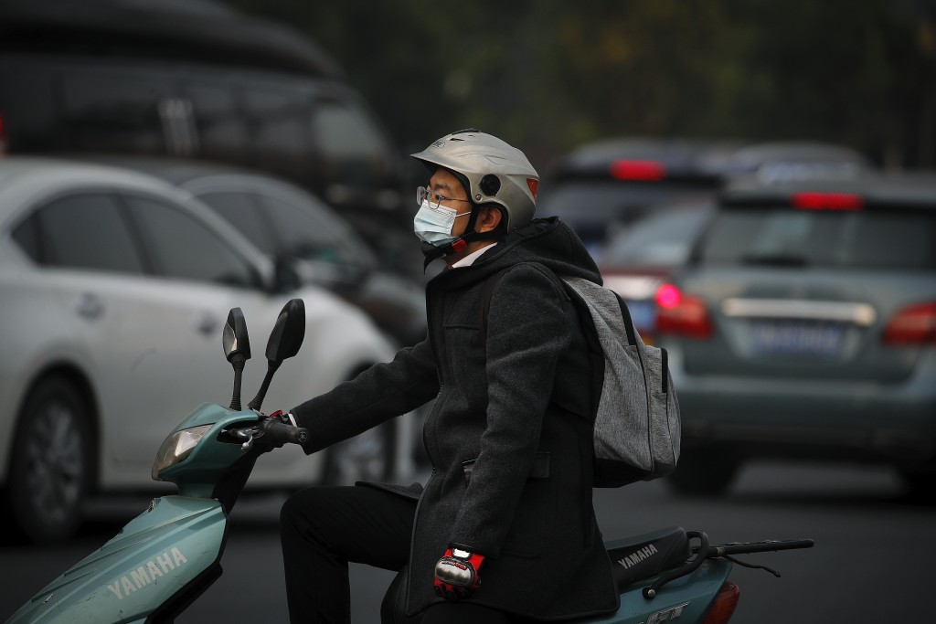 A man wearing a face mask to help curb the spread of the coronavirus rides on a scooter as he waits to cross a street during the morning rush hour in ...