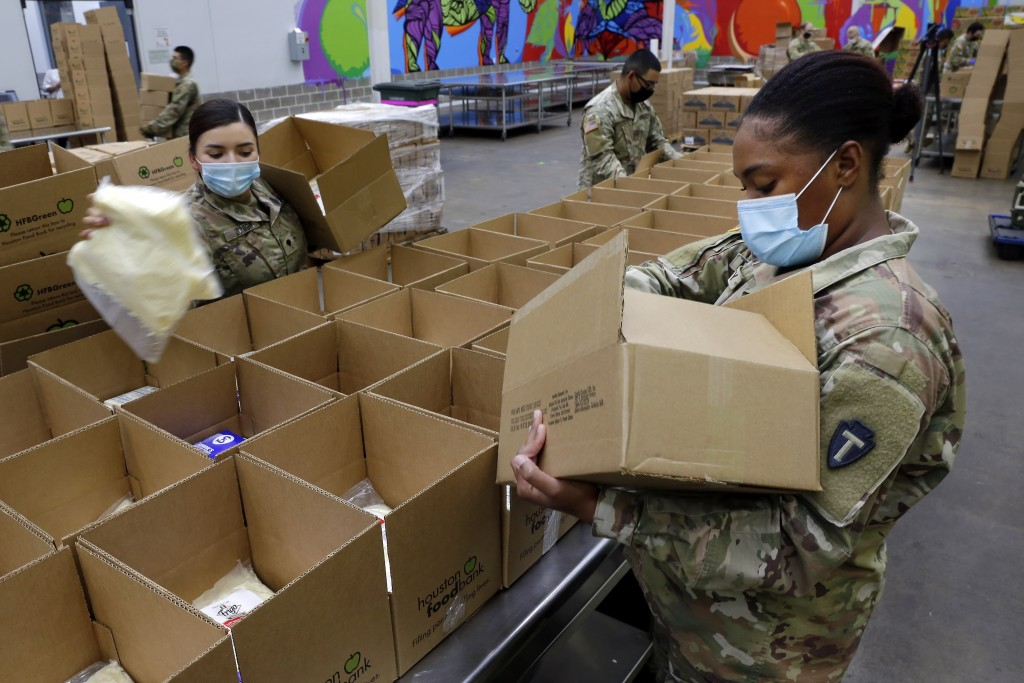 Texas National Guard soldiers Spc. Esmeralda Zuniga, left, and Spc. Samantha McClasky, right, load boxes with various dairy products such as milk, che...