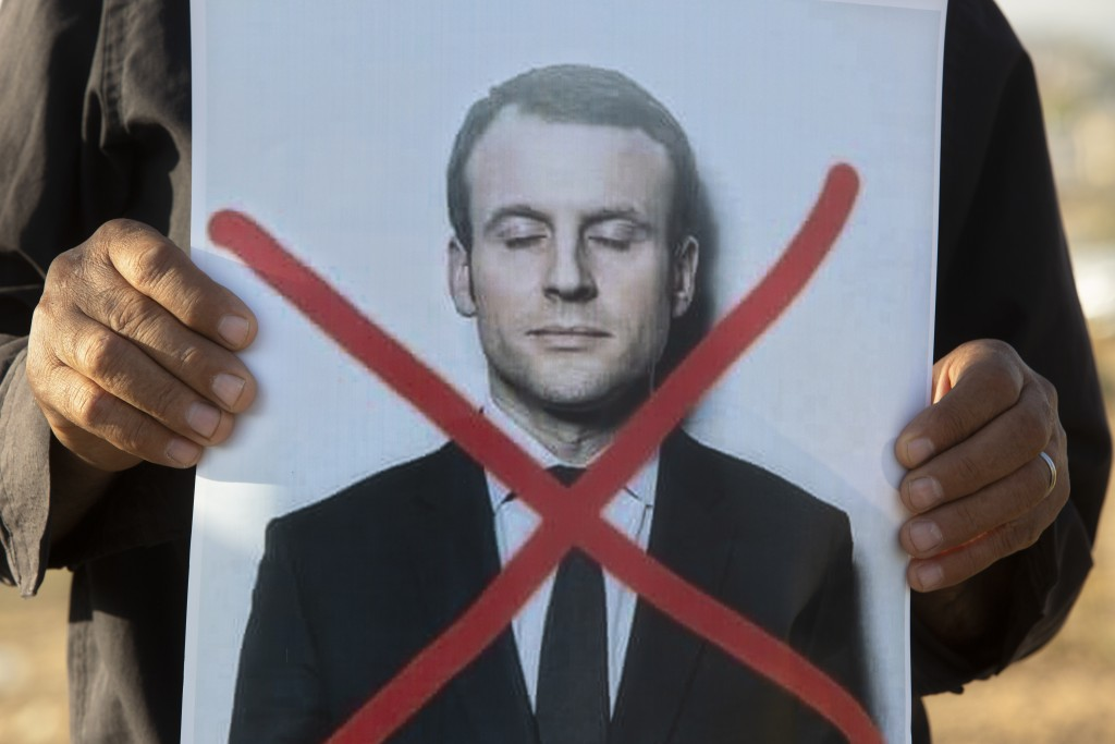 An Israeli Arab protester holds a defaced picture of French President Emmanuel Macron, during a small demonstration protesting published caricatures o...