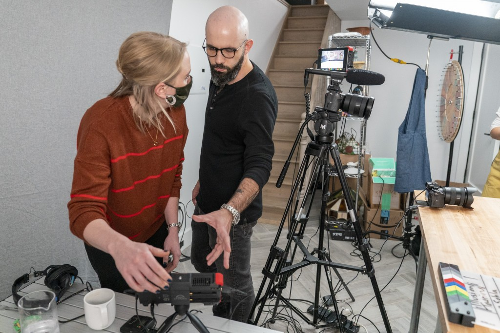 In this Oct. 7, 2020 photo, producer Jessica Opon, left, and Andrew Rea, founder of the Binging with Babish network, go over the framing of a scene du...