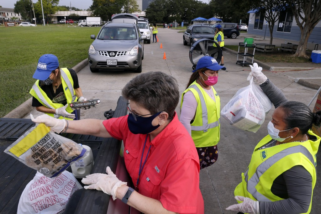 Volunteers load bags of food into the bed of a client's pick up truck in the drive thru line at the West Houston Assistance Ministries Wednesday, Oct....